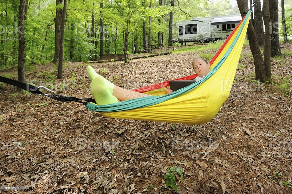 Teenager resting in hammock at campground royalty-free stock photo