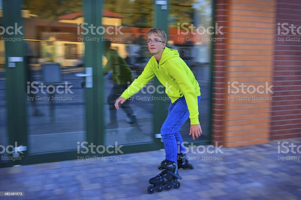 Teenager riding to the roller skating royalty-free stock photo