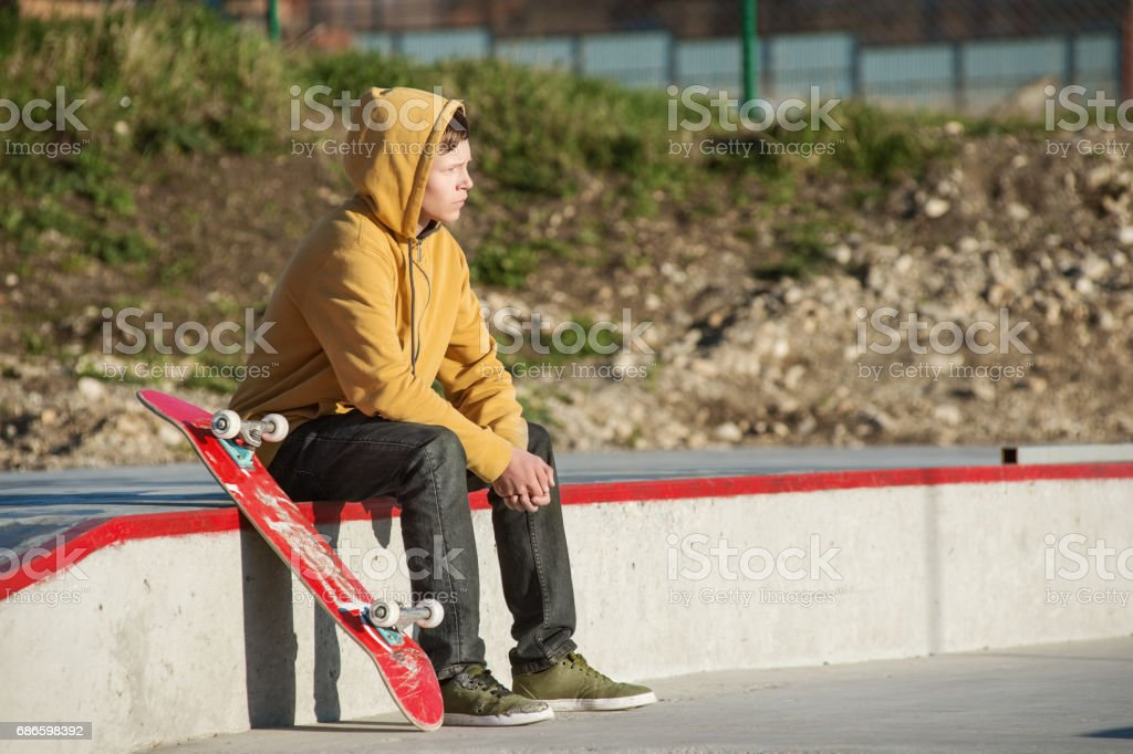 A teenager sitting in a yellow hoodie with a skateboard against a background of a city slum urban stock photo
