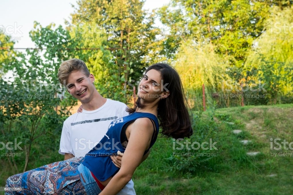 Teenager smiling, girl in boy's arms stock photo