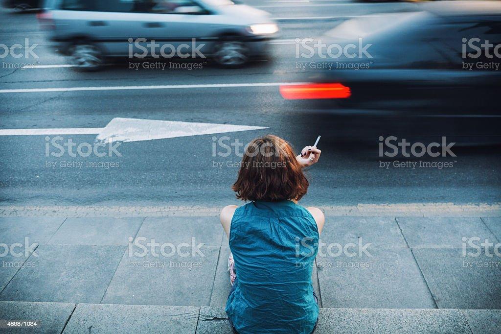 Teenager smoking on a sidewalk stock photo