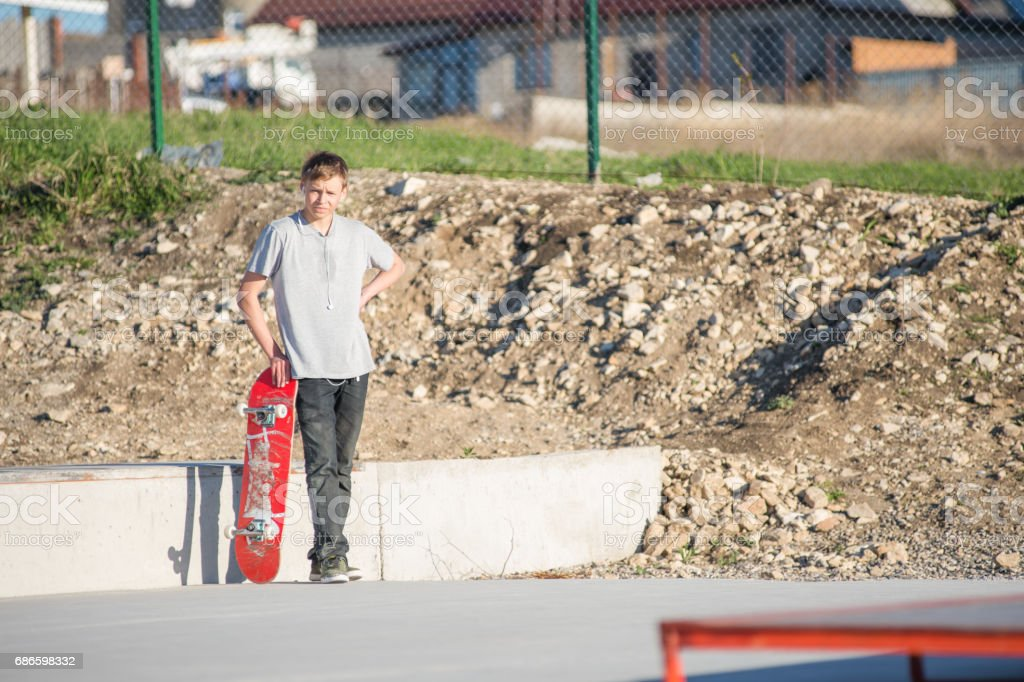 A teenager standing in a skatepark in a gray T-shirt with a skateboard in hand against the backdrop of the outskirts of the city stock photo