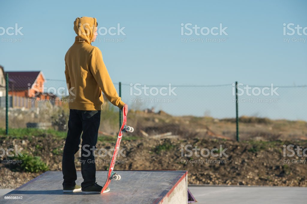 Teenager standing in a yellow hoodie holding a hand skateboard on the background urban slum stock photo