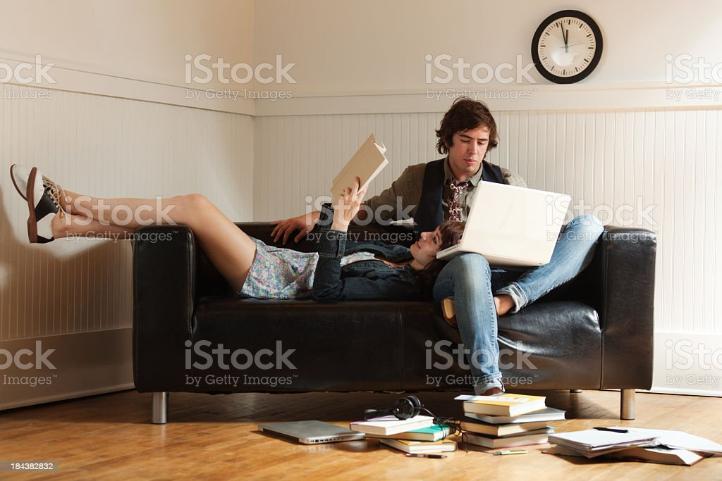 Teenager Student Couple Reading Laptop, Studying Together on Apartment Sofa stock photo