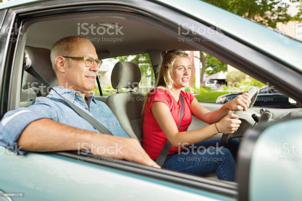 Teenager Student Driver Driving with Adult, Parent, or Father in Passenger Seat stock photo