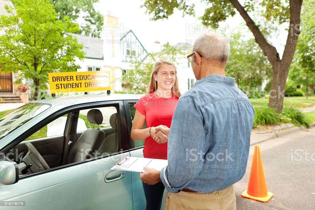 Teenager Student Driver Shaking hand with Driving Instructor Examiner stock photo