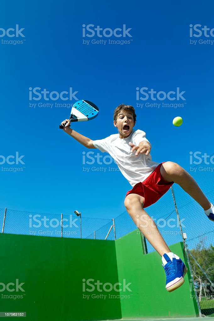 Teenager swinging a paddle to a tennis ball on a sunny day stock photo