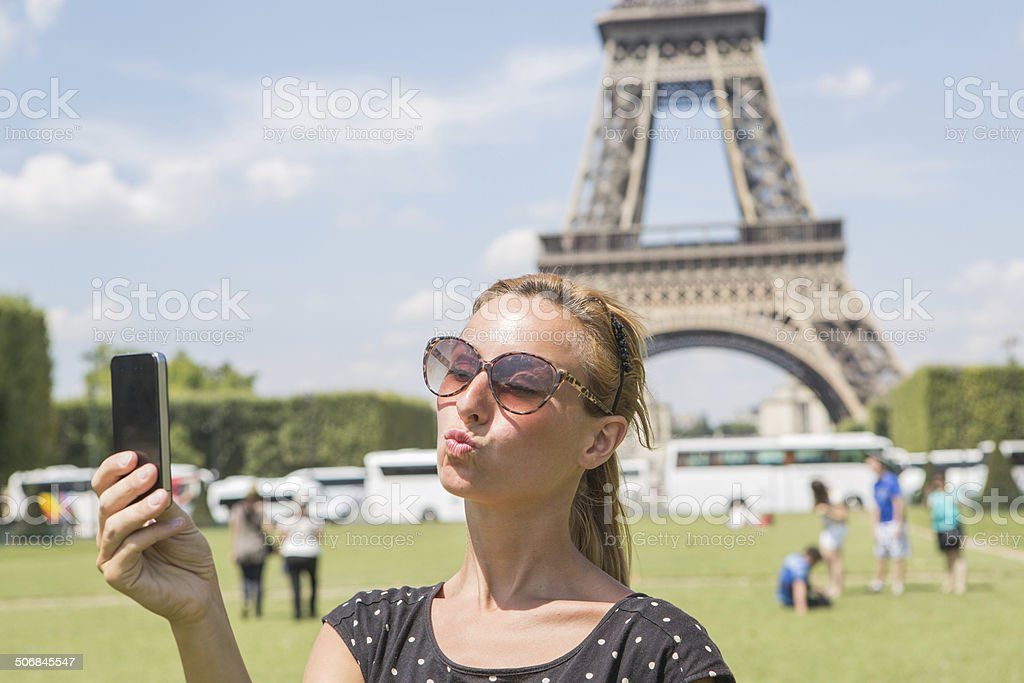 Teenager taking selfie with smartphone at Eiffel tower, Paris royalty-free stock photo