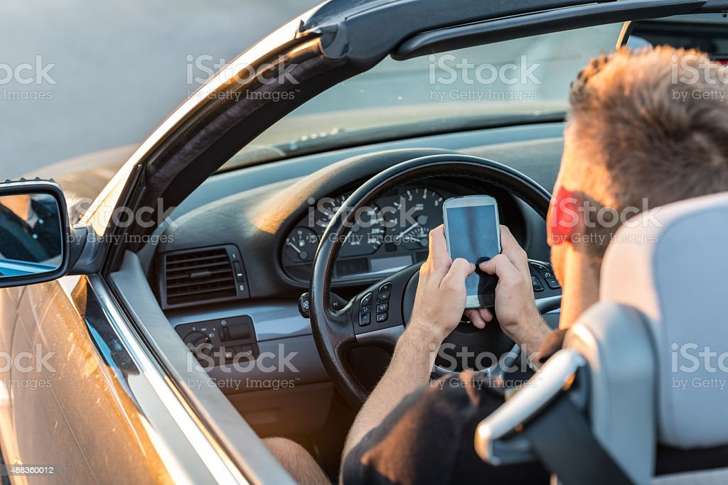 Teenager texting while driving stock photo