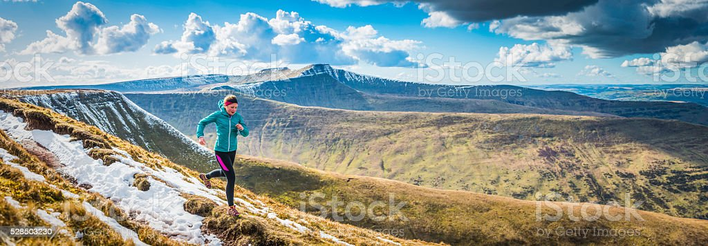 Teenager trail running along mountain path Brecon Beacons panorama Wales stock photo