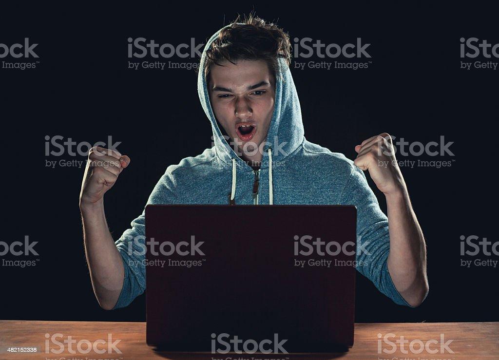 Teenager using laptop at night stock photo