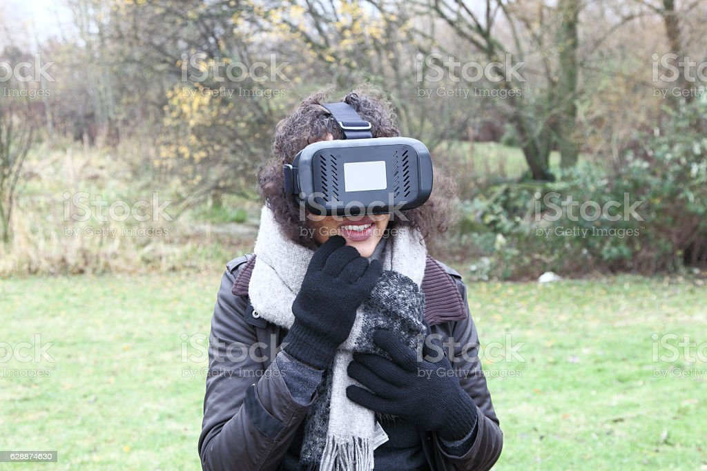 teenager using virtual reality simulator visor outdoors stock photo