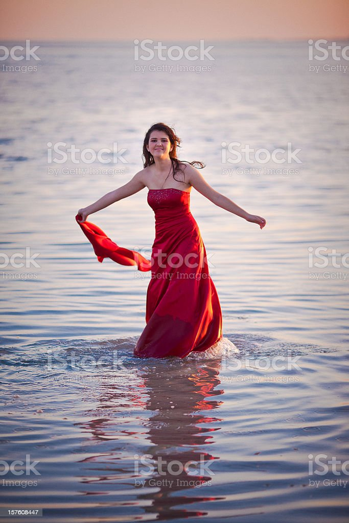teenager wearing a long red dress in the beach stock photo