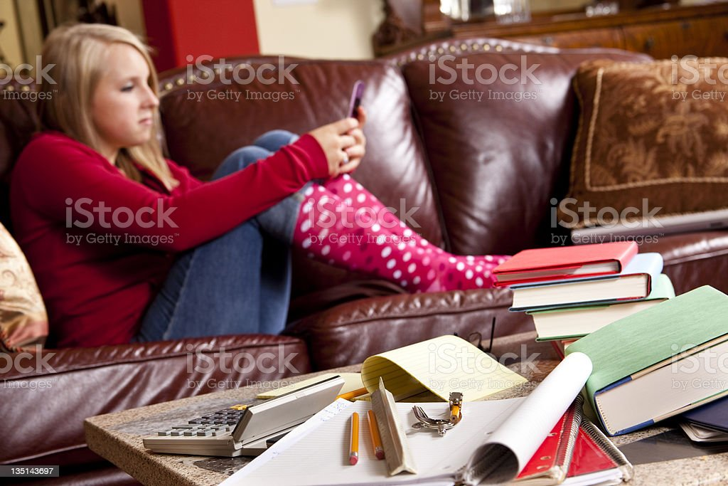 Teenager wearing polka dot socks on sofa texting  cell phone royalty-free stock photo
