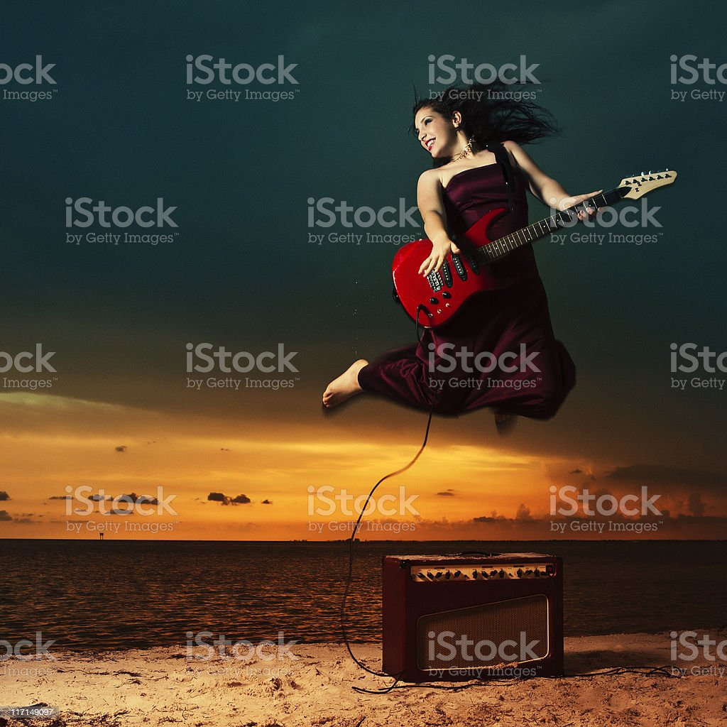 teenager with an electric guitar in the beach royalty-free stock photo