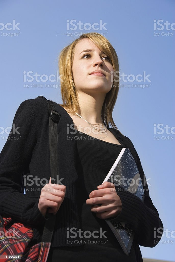 Teenager with backpack and notebook contemplating future royalty-free stock photo