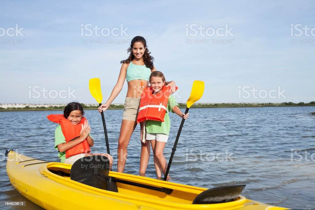 Teenager with girls beside kayak royalty-free stock photo