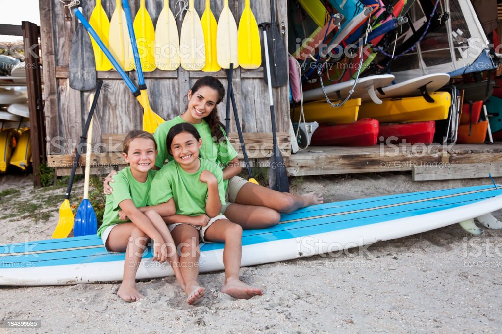 Teenager with girls sitting on paddle board stock photo
