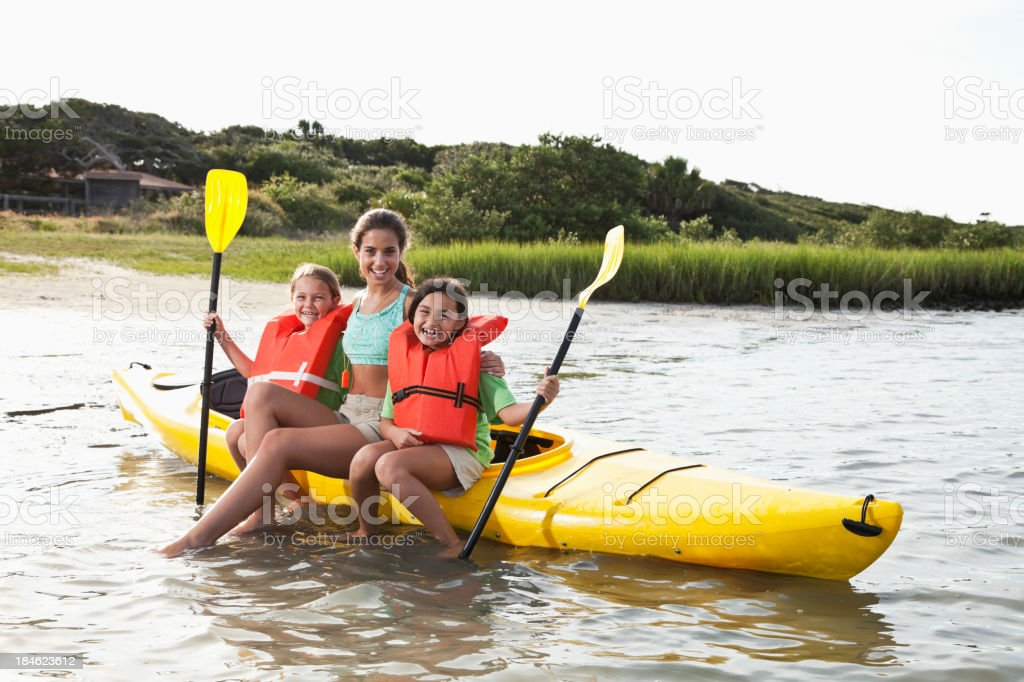 Teenager with little girls sitting on kayak stock photo