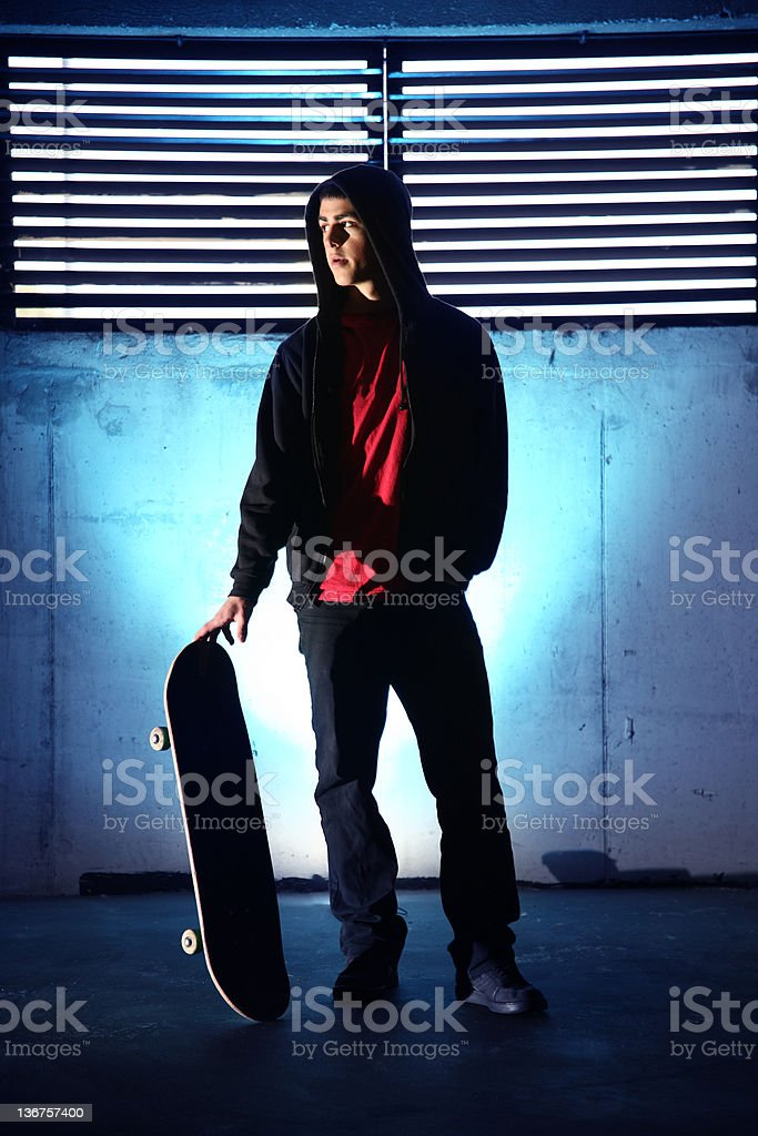 teenager with skateboard at night blue background royalty-free stock photo