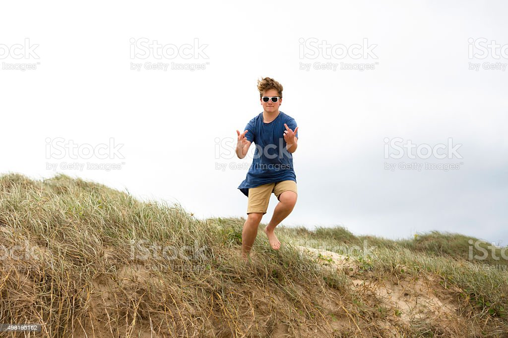 Teenager with sunglasses jumping and showing middle fingers, copy space stock photo