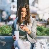 Teenager with take-away coffee using smart phone