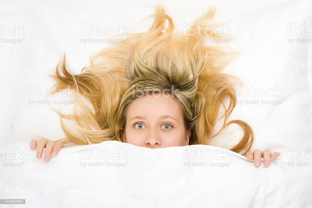 Teenager with wild hair in bed stock photo
