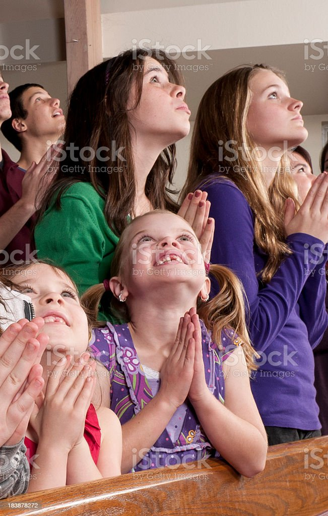 Teenagers and Little Girls, Hands Folded in Prayer, Looking Up stock photo