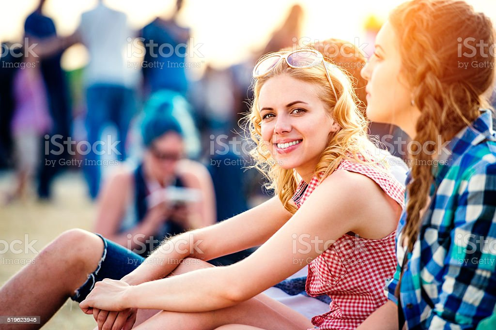 Teenagers at summer music festival, sitting on the ground stock photo