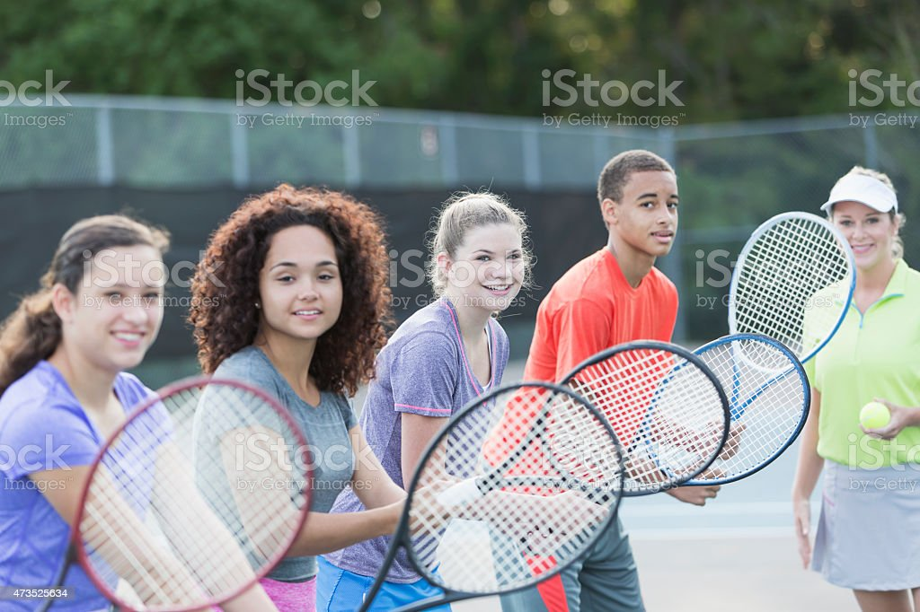 Teenagers at tennis clinic with instructor stock photo