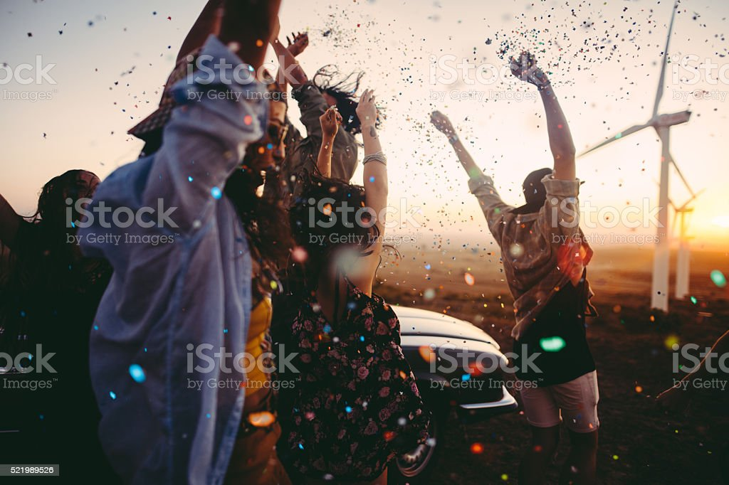 Teenagers celebrating with colourful confetti on summer road tri stock photo