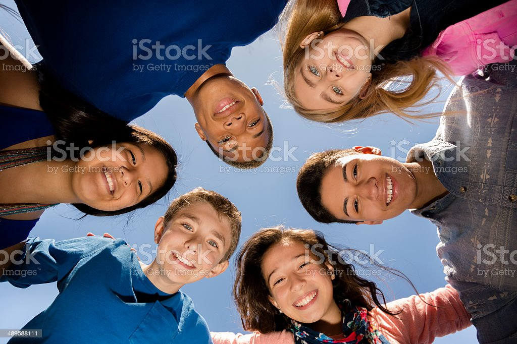 Teenagers: Diverse group of friends huddle outside together. Blue sky. stock photo