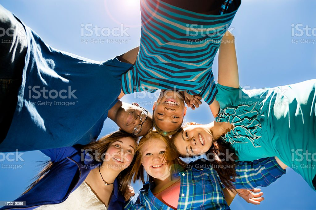 Teenagers: Group of friends hang out together. Blue sky. stock photo