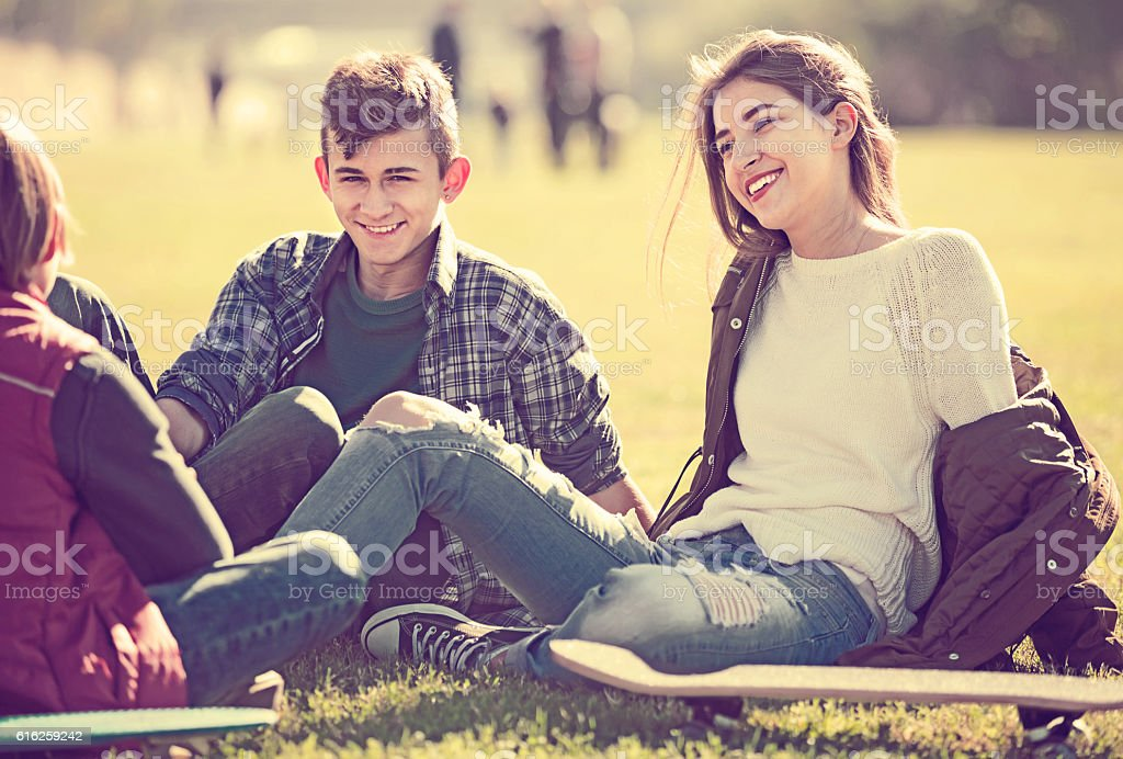 teenagers hanging out outdoors and discussing something stock photo