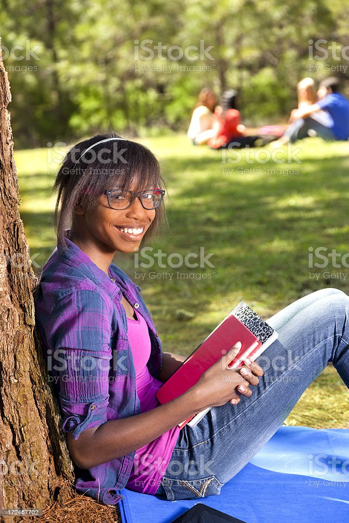 Teenagers: Happy female teen under tree with school books royalty-free stock photo