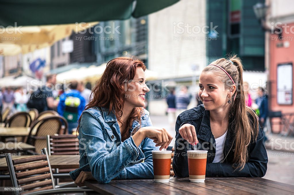 Teenagers having fun seated at an outdoor cafeteria stock photo