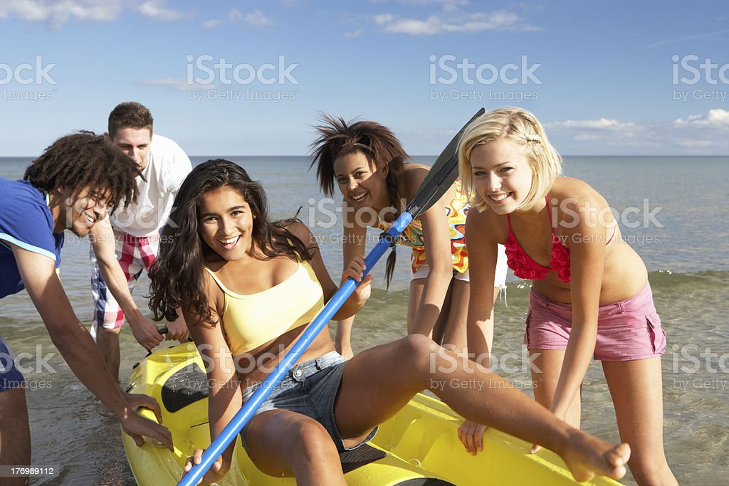 Teenagers in sea with canoe royalty-free stock photo