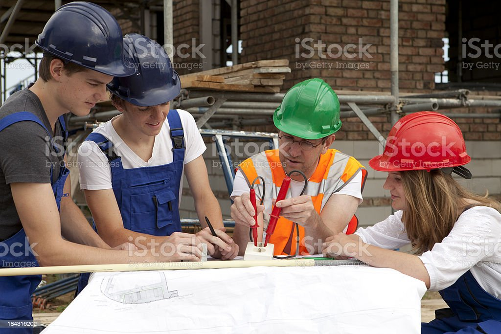 Teenagers learning a occupation. Trainee electrician. royalty-free stock photo