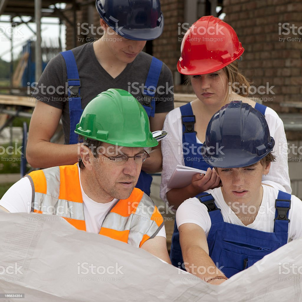 Teenagers learning a occupation. Trainee looking on blueprint royalty-free stock photo