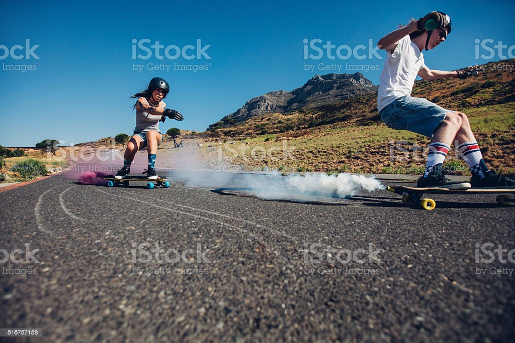 Teenagers longboarding on open road stock photo