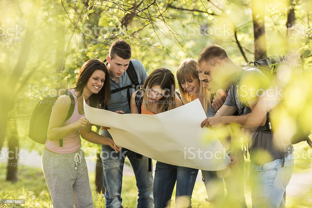 Teenagers looking at map. stock photo