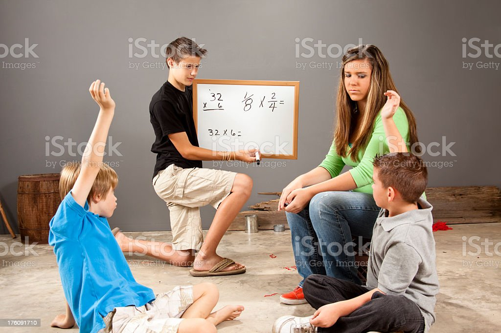 Teenagers mentoring elementary age boys royalty-free stock photo
