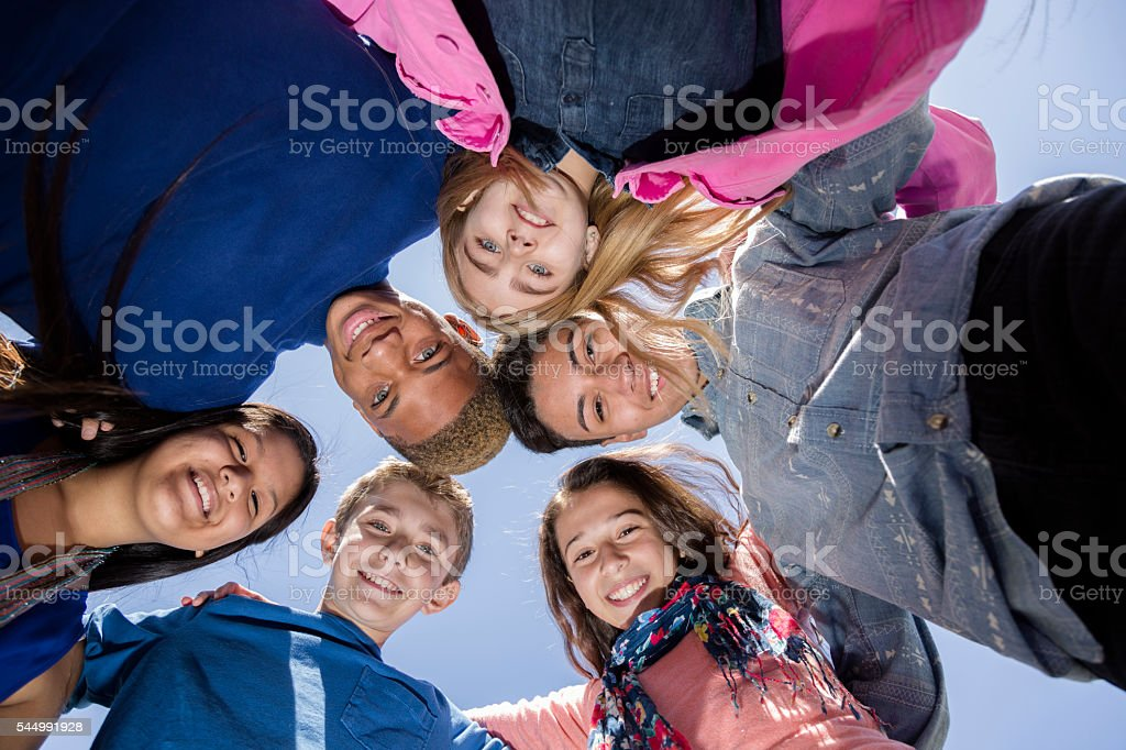 Teenagers: Multi-ethnic group of friends huddle outside together. Blue sky. stock photo