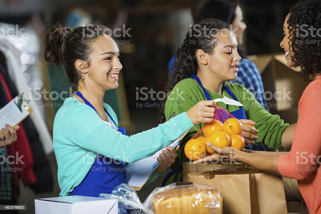 Teenagers passing out donations at food bank donation drive stock photo
