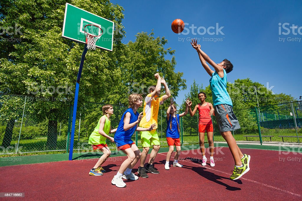 Teenagers playing basketball game together stock photo