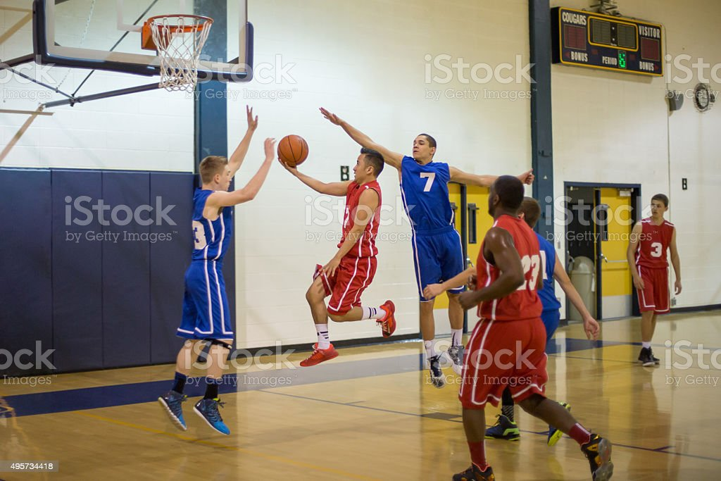 Teenagers playing basketball in gymnasium stock photo