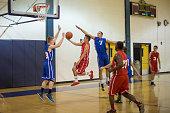 Teenagers playing basketball in gymnasium