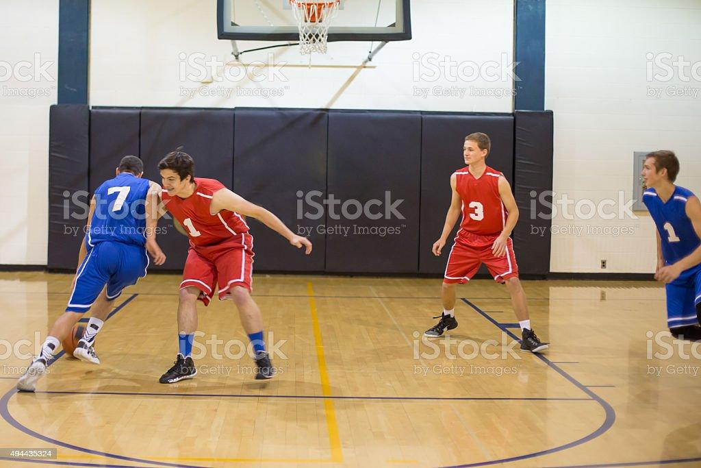 Teenagers playing high school basketball stock photo