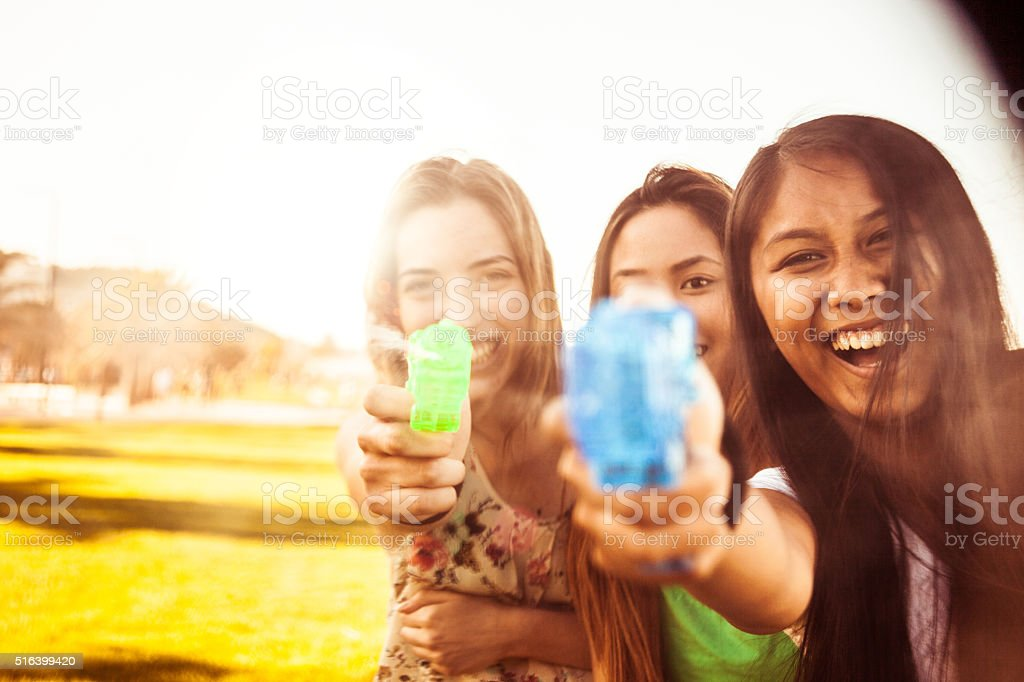 Teenagers playing holding water guns stock photo