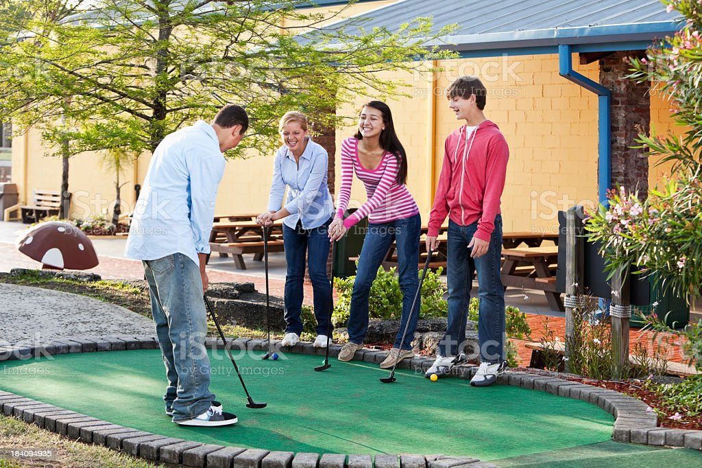 Teenagers playing miniature golf royalty-free stock photo